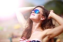 放松愉快的妇女在阳光下 免版税库存图片