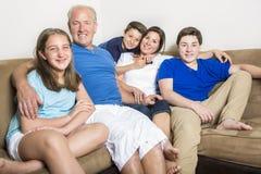 放松户内一起观看的电视的家庭 库存照片
