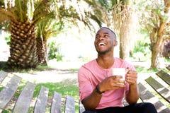 放松户外与一杯咖啡的英俊的年轻非洲人 免版税库存图片