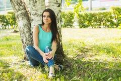 放松户外在草和微笑的妇女 库存图片
