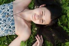 放松户外在草的微笑的妇女 免版税库存照片