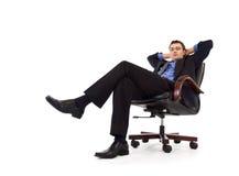 放松扶手椅子的生意人 图库摄影