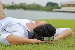 放松时间概念 听到与耳机的音乐的年轻亚裔人在自然背景中 免版税库存照片