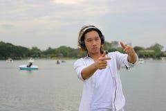 放松时间概念 反对耳机的愉快的年轻亚洲人本质上有拷贝空间背景 免版税库存照片