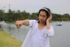 放松时间概念 反对耳机的愉快的年轻英俊的人在自然背景中 免版税库存图片