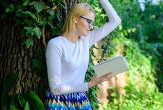 放松有书绿色自然背景的书痴学生 作为爱好的文学 花费与用的休闲 敏锐的女孩  库存照片