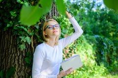 放松有书绿色自然背景的书痴学生 女孩敏锐对书继续读 妇女白肤金发的作为断裂 库存照片