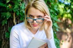 放松有书绿色自然背景的书痴学生 女孩敏锐对书继续读 镜片的逗人喜爱的书痴 免版税库存照片