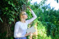 放松有书绿色自然背景的书痴学生 花费与用的休闲 女孩敏锐对书继续读 免版税图库摄影