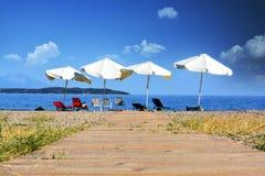放松概念、空的海滩与遮阳伞和椅子 库存照片