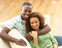 放松浪漫坐的沙发年轻人的夫妇 库存图片