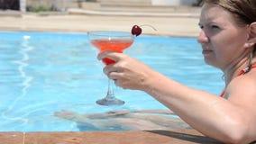 放松用一个新鲜的西瓜或草莓用一棵樱桃在玻璃鸡尾酒,饮料坐的泳装的年轻女人 股票视频