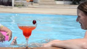 放松用一个新鲜的西瓜或草莓用一棵樱桃在玻璃鸡尾酒,饮料坐的泳装的年轻女人 股票录像
