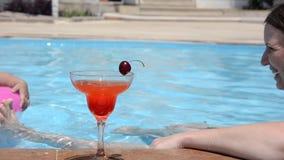 放松用一个新鲜的西瓜或草莓用一棵樱桃在玻璃鸡尾酒,饮料坐的泳装的年轻女人 影视素材