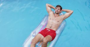 放松用在头后的手的人在游泳场4k的可膨胀的管 股票录像
