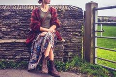 放松由农村石墙的妇女 免版税库存照片