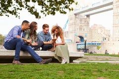 放松由塔桥梁的小组朋友在伦敦 免版税库存照片