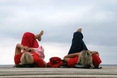 放松由天空背景的,软的焦点海的两个女孩 库存照片