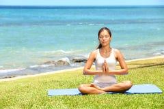 放松由海的瑜伽妇女思考的妇女 免版税库存图片