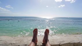 放松由海洋的人的脚在与清楚的蓝天的一个晴天 影视素材