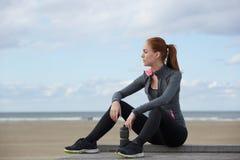放松由海滩的可爱的体育妇女在锻炼以后 库存照片