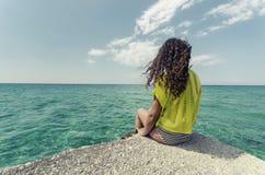 放松由海洋的青少年的女孩 免版税库存照片