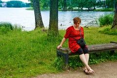 放松由湖的中年妇女 免版税库存图片