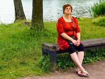 放松由湖的中年妇女 图库摄影