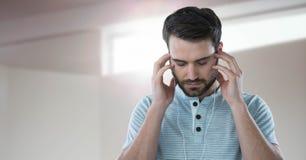 放松由窗口光的耳机的被注重的人 库存照片