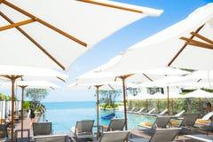 放松的人们和享用在Th的豪华无限游泳池 免版税库存照片