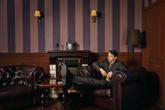 放松的商人,当坐在一把皮革行政椅子时 免版税库存照片