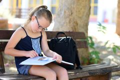 放松的夏时-女孩看书室外在温暖的天 免版税库存图片