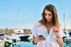 放松的女孩,当earing音乐在船坞时 免版税库存照片