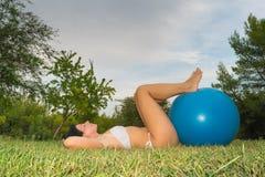 放松的妇女做一些pilates行使与fitball 库存照片