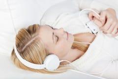 放松的妇女,当在耳机时的听的音乐 免版税库存照片