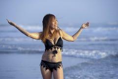 放松的年轻美好和性感愉快亚洲妇女微笑获得在热带海滩的乐趣在巴厘岛亚洲 免版税库存照片