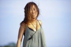 放松的年轻美好和性感愉快亚洲妇女微笑获得在热带海滩的乐趣在巴厘岛亚洲 免版税库存图片