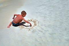 放松的概念在夏天海的 海滨的逗人喜爱的男孩绘在沙子的微笑的太阳 孩子绘兴高采烈的面孔顶视图拷贝空间 库存照片