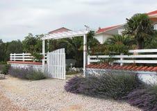 放松的欢迎在一个舒适地方 白色篱芭和开放门 库存照片
