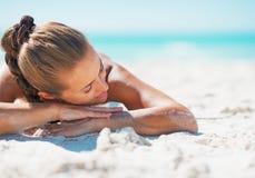 放松的泳装的愉快的妇女,当放置在海滩时 库存图片