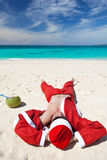 放松的海滩的圣诞老人 免版税库存图片