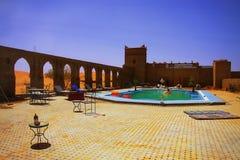 放松的片刻在一片旅馆游泳池amids摩洛哥沙漠,有在天际的沙丘的 库存照片