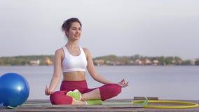 放松的瑜伽,莲花坐的年轻可爱的信奉瑜伽者女孩思考并且使在自然的精神calmnes高兴 股票录像