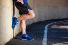 放松的男性赛跑者倾斜 免版税库存照片