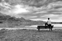 放松的长木凳在岸 观看在阿尔卑斯山用白色峰顶镜子 库存图片