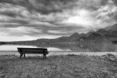 放松的长木凳在岸 观看在阿尔卑斯山用白色峰顶镜子 库存照片