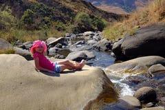 放松的年轻假期女孩在河 免版税库存图片