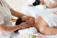 放松美丽的亚裔的女孩接受在温泉的面部按摩 图库摄影