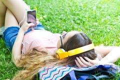 放松美丽的女孩和听在耳机的音乐在Th 免版税图库摄影
