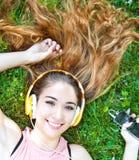 放松美丽的女孩和听在耳机的音乐在Th 免版税库存照片